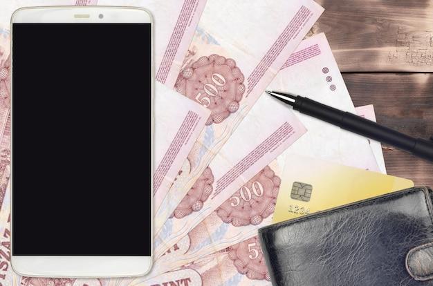 Factures en forint hongrois et smartphone avec sac à main et carte de crédit