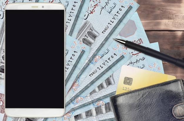 Factures en livres égyptiennes et smartphone avec sac à main et carte de crédit