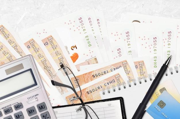 Factures en livres sterling et calculatrice avec lunettes et stylo