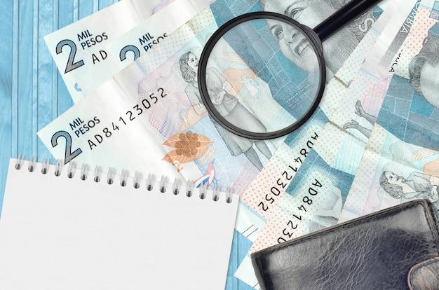 Factures de pesos colombiens et loupe avec sac à main noir et bloc-notes