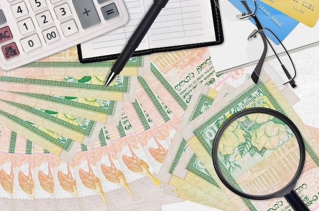 Factures de roupies sri lankaises et calculatrice avec lunettes et stylo