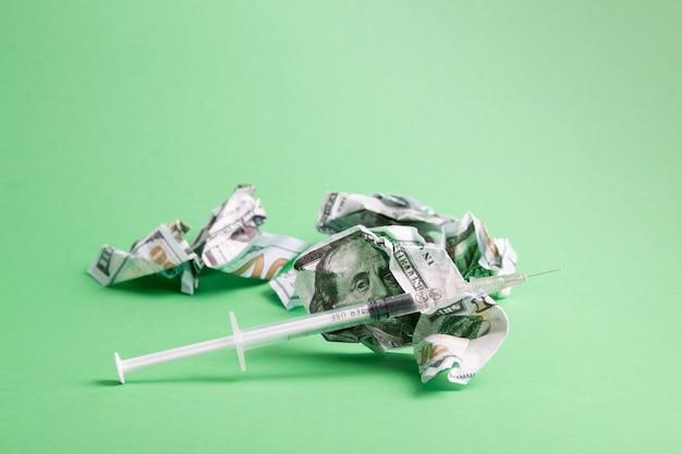 Factures stallaires froissées et seringue à insuline fond vert, espace copie