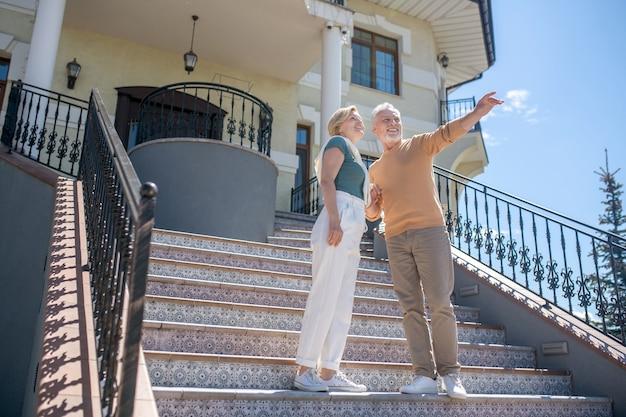 Faible angle d'un bel homme aux cheveux gris souriant et de sa femme heureuse debout sur les escaliers de luxe