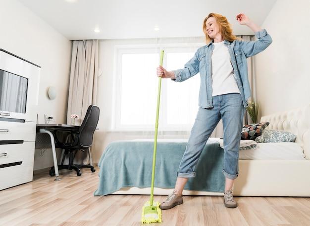 Faible angle de femme s'amuser tout en épongeant le sol