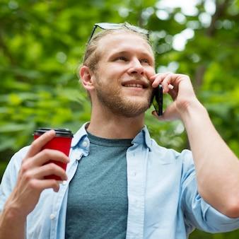 Faible angle d'homme gai parlant au téléphone