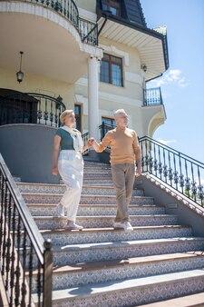 Faible angle d'une jolie femme blonde souriante et d'un homme aux cheveux gris satisfait descendant les escaliers de luxe
