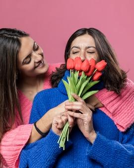 Faible angle mère sentant les fleurs de la fille