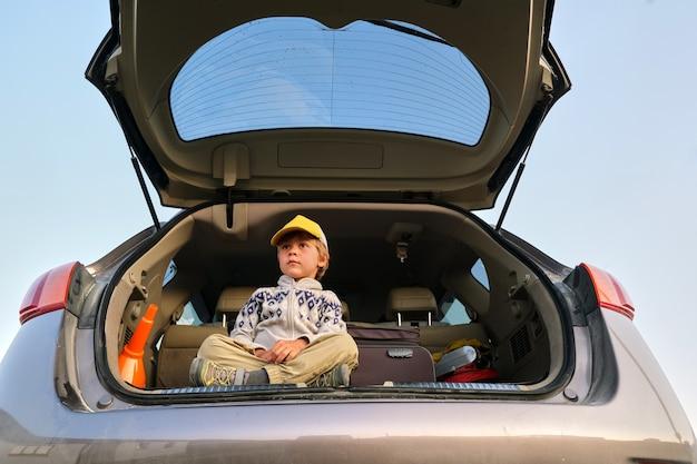 Faible angle de petit garçon rêveur en sweat à capuche et casquette assis avec les jambes croisées dans le coffre ouvert d'une automobile moderne avec valise avant le voyage d'été