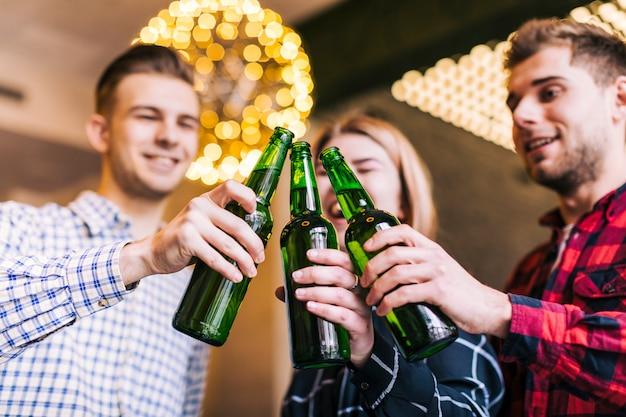 Faible angle de vue des amis heureux tinter des bouteilles de bière