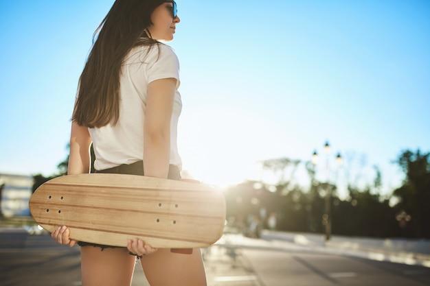 Faible angle vue arrière élégante fille patineuse brune souriante rêveuse