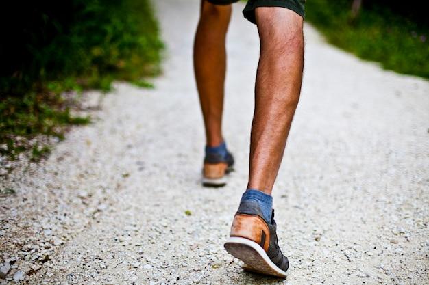 Faible angle de vue au niveau du sol avec les pieds d'un homme sur un chemin de parc ou de forêt.