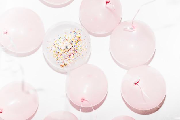Faible angle de vue des ballons d'anniversaire avec des banderoles sur fond blanc