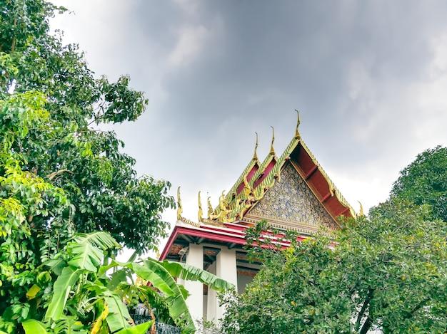 Faible angle de vue de la construction d'un temple bouddhiste à travers les arbres contre le ciel nuageux