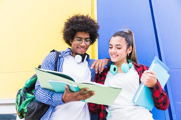 Faible angle de vue d'un couple d'adolescents lisant le livre debout contre un mur coloré