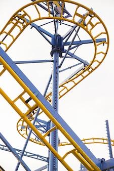 Faible angle de vue du chemin de fer de montagnes russes au parc d'attractions