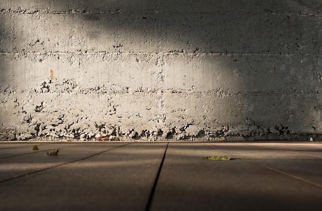 Faible angle de vue du plancher en bois pour brouiller le mur de béton grunge avec la lumière du soleil