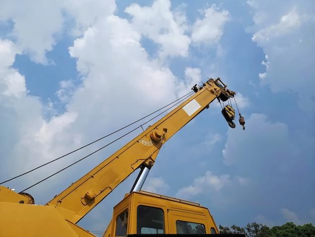 Faible angle de vue de la flèche télescopique avec grue de grue jaune sur un chantier de construction contre le ciel nuageux