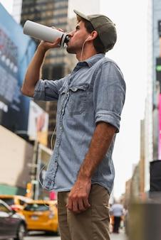 Faible angle de vue avec homme buvant au thermos