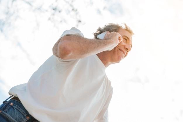 Faible angle de vue d'un homme souriant, parlant au téléphone portable debout sous le ciel