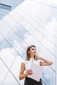 Faible angle de vue de la jeune femme d'affaires debout près des documents de construction d'entreprise