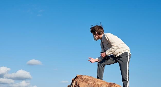 Un faible angle de vue d'un jeune homme d'espagne avec des jumelles portant un masque debout sur une montagne étonné par la vue