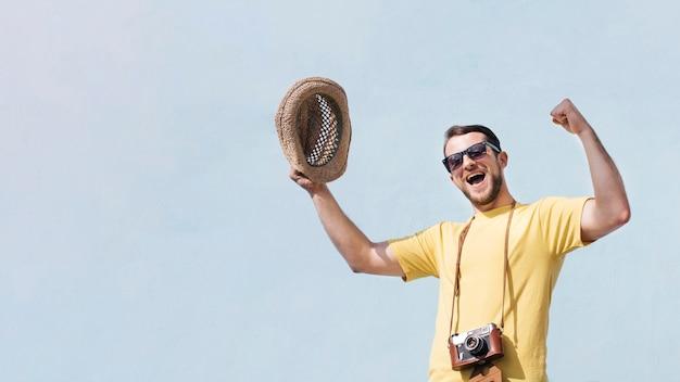 Faible angle de vue de jeune homme excité, serrant son poing et hurlant contre le ciel