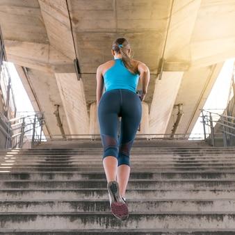 Faible angle de vue de jogger féminin en cours d'exécution sur l'escalier sous le pont
