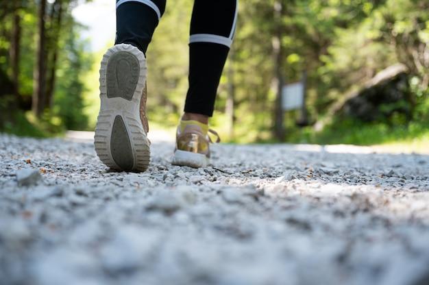 Faible angle de vue des pieds féminins en randonnée sur un sentier dans une belle forêt verte.