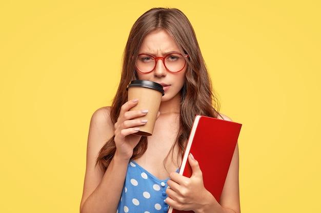 Faible esprit jeune femme avec des lunettes posant contre le mur jaune