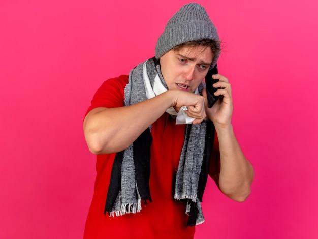 Faible jeune bel homme malade blonde portant chapeau d'hiver et écharpe parler au téléphone tenant la serviette en gardant la main près de la bouche regardant vers le bas isolé sur fond cramoisi avec espace de copie