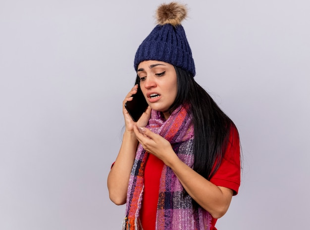 Faible Jeune Fille Malade De Race Blanche Portant Chapeau D'hiver Et écharpe Parler Au Téléphone En Gardant La Main Dans L'air Regardant Vers Le Bas Isolé Sur Fond Blanc Avec Copie Espace Photo gratuit