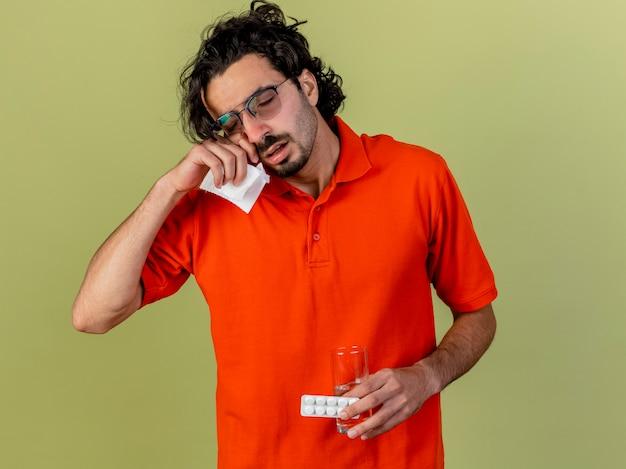 Faible jeune homme malade de race blanche portant des lunettes tenant un verre d'eau pack de comprimés et serviette touchant le visage isolé sur fond vert olive