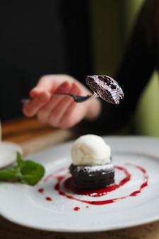 Faible profondeur de la photo du gâteau au brownie avec de la glace. main de jeune fille avec une fourchette.