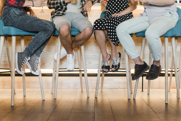 Faible section d'amis assis sur un tabouret de bar