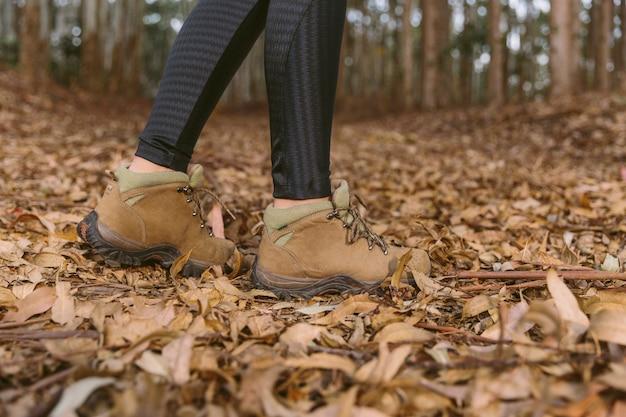 Faible section de femme debout sur des feuilles sèches