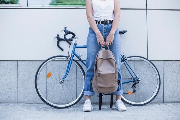 Faible section de jeune femme tenant le sac à dos dans sa main, debout contre le vélo