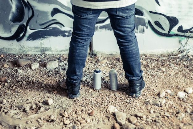 Faible section vue du pied d'un homme avec des bombes aérosols