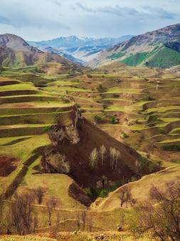 Faille dans la roche. paysage de montagne verte unique avec des terrasses vertes et un ciel bleu nuageux. coupe géologique, faille en distance. arrière-plan de roches inimaginables.