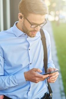 Faire un appel important jeune bel homme d'affaires portant des écouteurs sans fil à l'aide d'un smartphone tout en