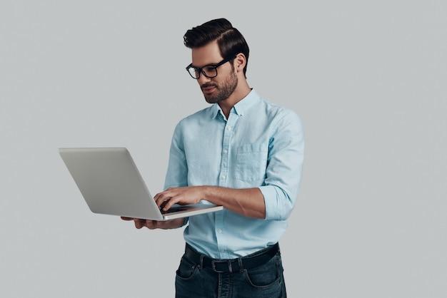 Faire attention à chaque détail. jeune homme utilisant un ordinateur portable en se tenant debout sur fond gris