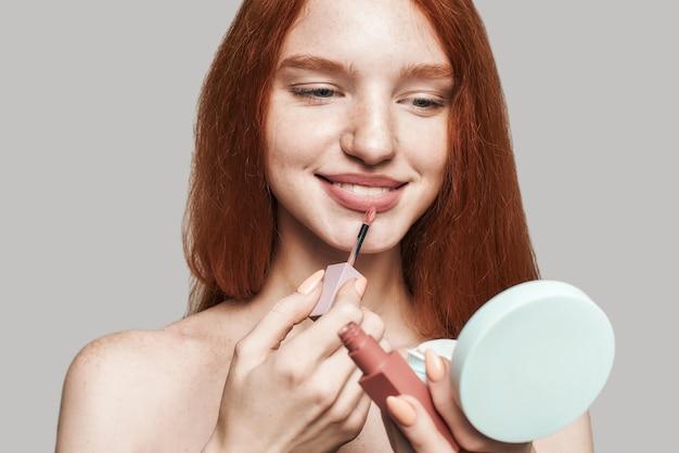 Faire de la beauté. portrait d'une jolie jeune femme aux longs cheveux roux peignant les lèvres avec un crayon à lèvres et regardant le petit miroir en se tenant debout sur fond gris. composez le concept. produit de beauté