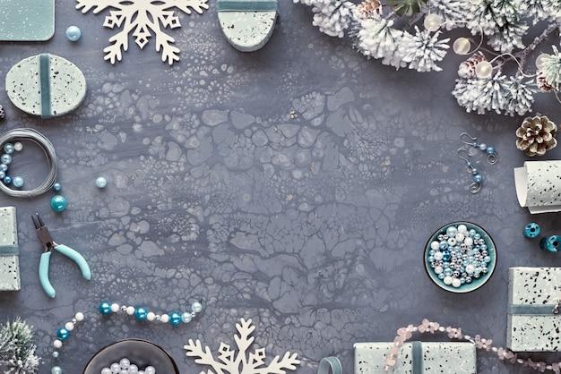 Faire des bijoux faits à la main pour des amis comme cadeaux de noël. mise à plat sur fond texturé sombre.