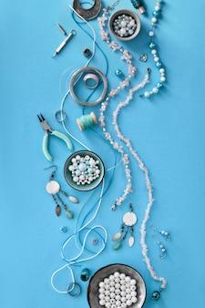 Faire des bijoux à la main. mise à plat sur papier couleur menthe.