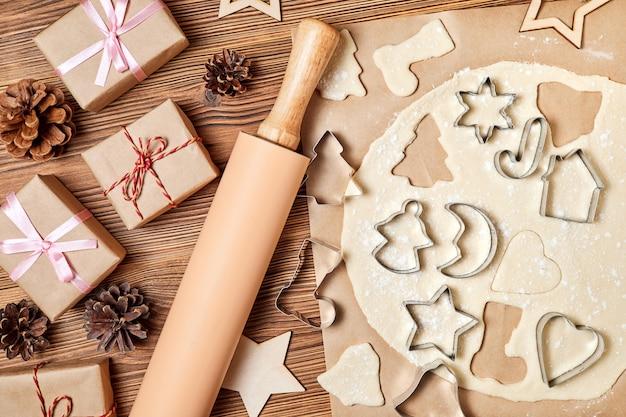 Faire des biscuits de noël en pain d'épice à l'aide d'un formulaire pour cuisiner sur fond de bois