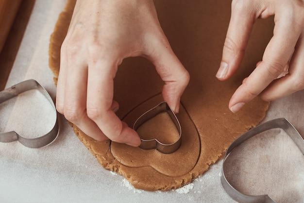 Faire des biscuits de pain d'épice en forme de coeur pour la saint valentin. main de femme utilise un emporte-pièce. concept de nourriture de vacances