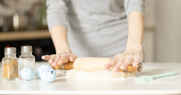 Faire des biscuits de pâques, des mains féminines avec de la pâte