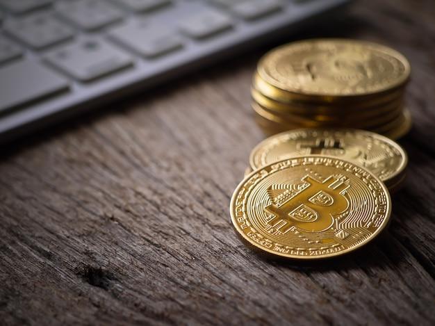 Faire des bitcoins de couleur dorée sur le clavier et la table de travail avec une vue rapprochée