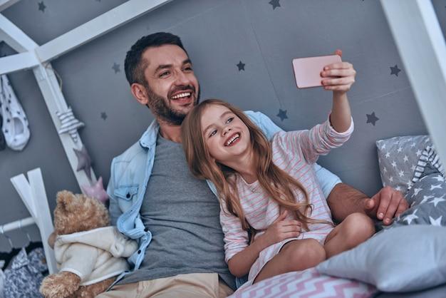 Faire de bons souvenirs. jeune père et sa petite fille prenant un selfie assis sur le lit à la maison