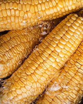 Faire bouillir les balançoires de maïs dans une casserole avec de l'eau. gros plan de maïs, bulles d'eau.