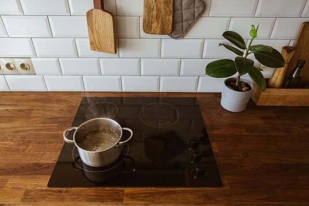 Faire bouillir de l'eau dans une marmite et une casserole sur une cuisinière à induction dans la cuisine blanche moderne